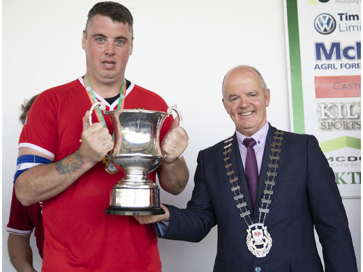 Ballina United's Trevor Marshall receives the McDonnell Cup from Blackie Gavin